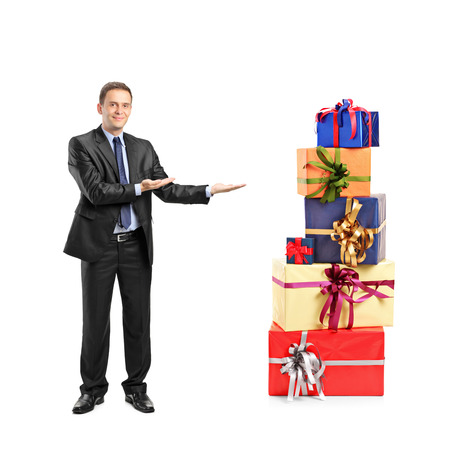 Full length portrait of a man in suit gesturing and pile of gifts isolated on white background photo
