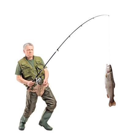 botas altas: Retrato de cuerpo entero de un pescador maduro captura de un pez aislado en fondo blanco
