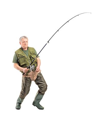 botas altas: Retrato de cuerpo entero de un pescador maduro que sostiene trole aislado en fondo blanco