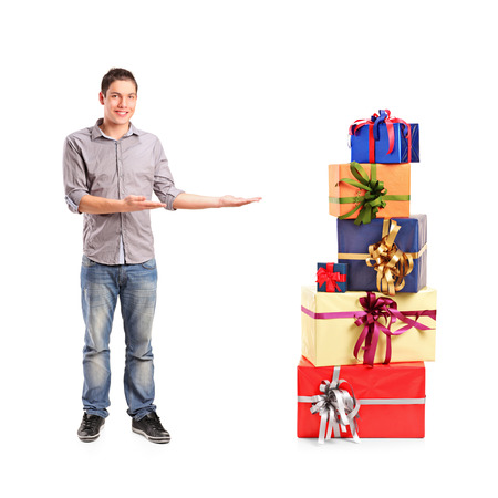 Full length portrait of a smiling gesturing and pile of gifts isolated on white background photo