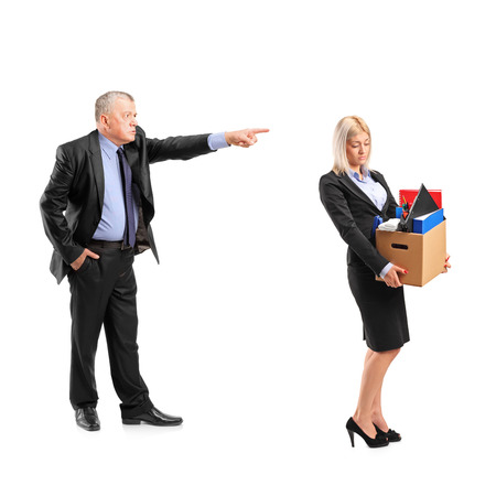 Full length portrait of an angry boss firing a woman in a suit carrying a box of personal items isolated on white background Stock Photo - 22362452