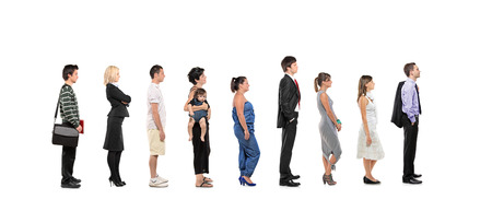 waiting in line: Full length portrait of men and women standing together in a line isolated on white background
