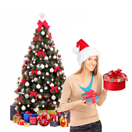 Happy female wearing christmas hat and holding gifts, christmas tree in the background photo