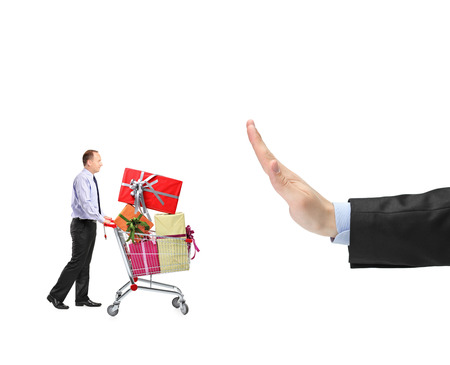 Man pushing a shopping cart full with presents and a hand gesturing stop isolated on white background Stock Photo - 22426009