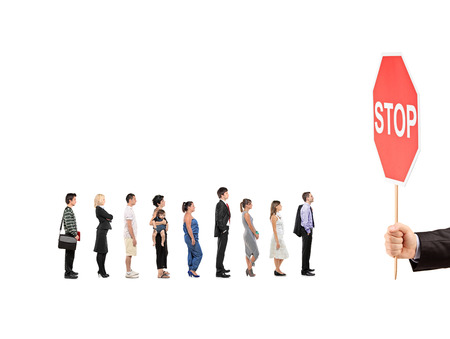 People waiting in line and a hand holding a stop traffic sign isolated on white background photo