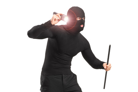 Robber with robbery mask holding a flashlight and piece of pipe isolated on white background photo