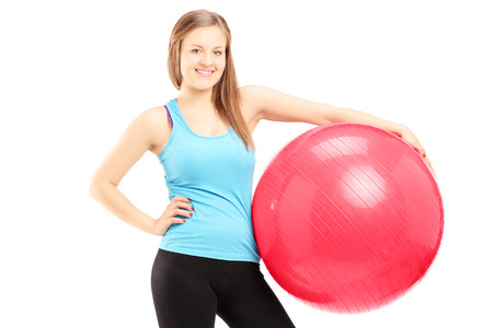 Young female athlete holding a fitness ball isolated against white background Stock Photo - 22425952