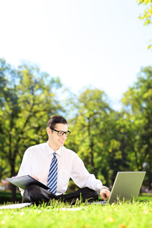 laptop outside: Young businessman seated on a green grass working on a laptop and writing down notes in a park