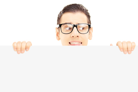 Scared young male with glasses hiding behind a blank panel isolated against white background photo