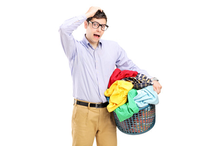 Young man holding a laundry basket and gesturing isolated on white background photo
