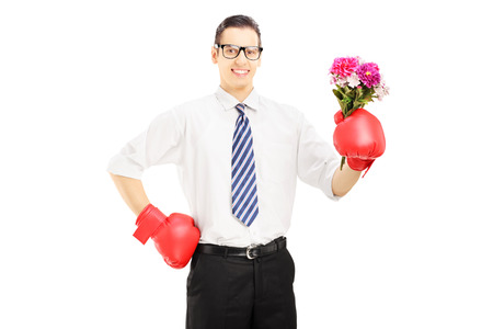 Smiling man with boxing gloves holding a bunch of flowers isolated against white background photo