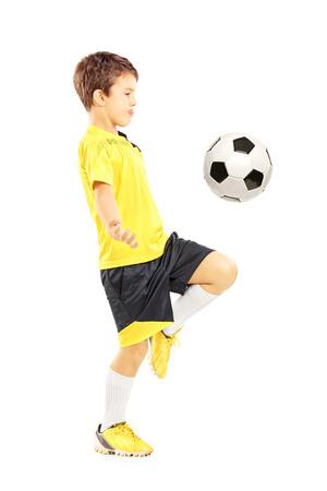 Volledige lengte portret van een kind in sportkleding joggling met een voet bal geïsoleerd op witte achtergrond