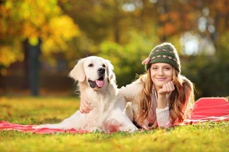 mujer con perro: Hembra bonita que se acuesta con su perro perdiguero de Labrador en un parque Foto de archivo
