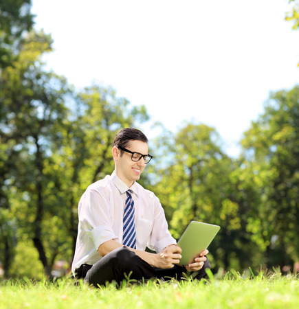 Young businessperson with glasses sitting on a green grass and working on a tablet in a park, shot with a tilt and shift lens photo