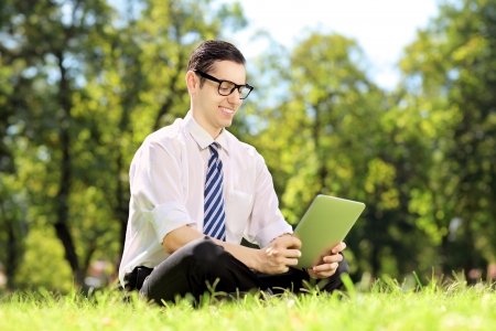 Young businessperson with glasses seated on a green grass working on a tablet in a park photo