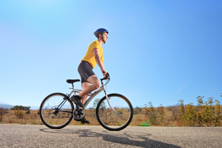Young male with helmet riding a mountain bike on a sunny day