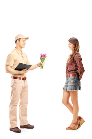Full length portrait of a delivery boy holding a bunch of flowers and woman isolated on white background photo