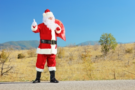 Full length portrait of a santa claus with bag full of gifts hitchiking on an open road  photo