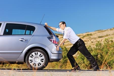 Jeune homme poussant sa voiture cassée ou une voiture en panne d'essence, sur une journée ensoleillée Banque d'images