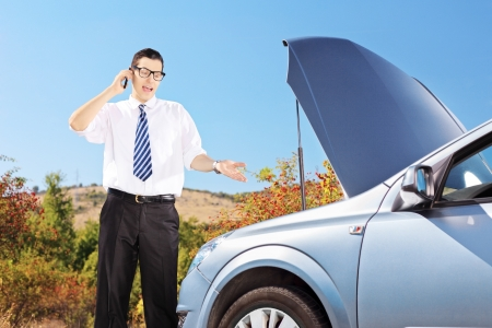 Young man standing near a broken car and talking on a cell phone, on a sunny day photo