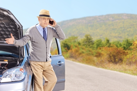 car trouble:  Nervous senior man on a broken car talking on a cell phone