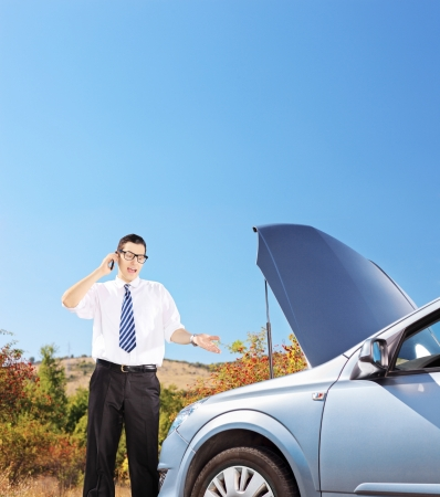 Young businessman standing near a broken car and talking on a mobile phone, shot with a tilt and shift lens photo