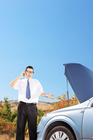Young businessman standing near a broken car and talking on a mobile phone photo