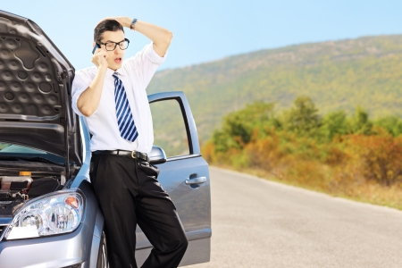 Young sad male on a broken car talking on a cell phone photo