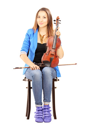 solo violinist: Casual young woman seated on a wooden chair holding a violin isolated on white background Stock Photo