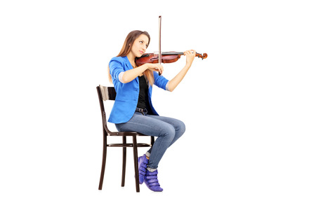Casual young woman seated on a wooden chair playing the violin isolated on white background photo