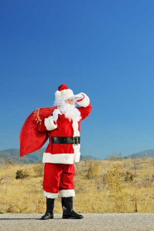 Full length portrait of a Santa claus with bag full of gifts standing on an open road and looking photo