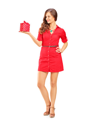 Full length portrait of an attractive smiling woman in red dress holding a gift isolated on white background photo