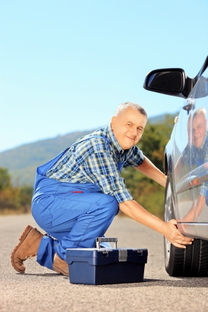Male mechanic changing a car tyre on an open road photo
