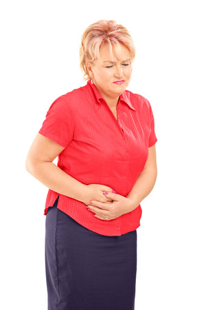 cramping: Mature blond female suffering from a stomach ache isolated on white background   Stock Photo