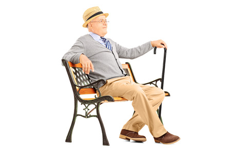 persona mayor: Hombre mayor Relaxed que se sienta en un banco de madera y pensamiento aislado en fondo blanco