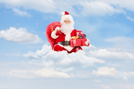 Santa Claus holding a bag full of presents and sitting on clouds photo