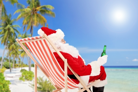 Santa Claus lying on a beach chair and drinking cold beer, enjoying on a sunny day, on a beach