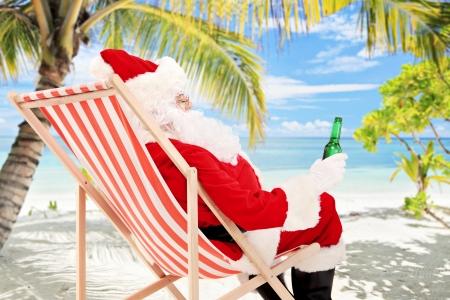 Kerstman op een strandstoel bier drinken en genieten op een zonnige dag, op een tropisch strand