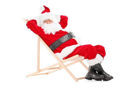 Smiling Santa Claus on a beach chair looking at camera isolated on white background photo