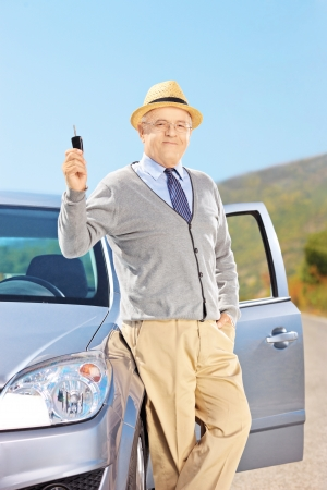 Smiling senior male holding a car key next to his automobile outside photo