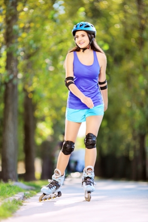 rollerblade: Full length portrait a young smiling female on rollers skating in a park