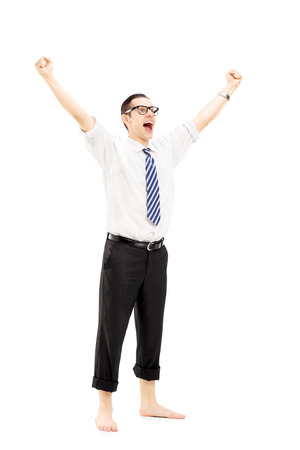 barefooted: Full length portrait of an excited barefooted guy with raised hands gesturing happiness isolated on white background Stock Photo