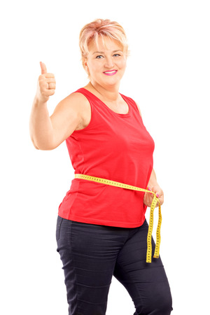 Happymature woman measuring her waist after diet and giving thumb up, isolated on white background