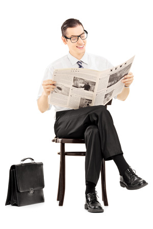 Young businessman sitting on a wooden bench and reading a newspaper isolated against white background photo