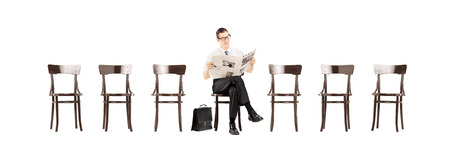 Young businessman sitting on a wooden bench and reading a newspaper while waiting isolated on white background photo