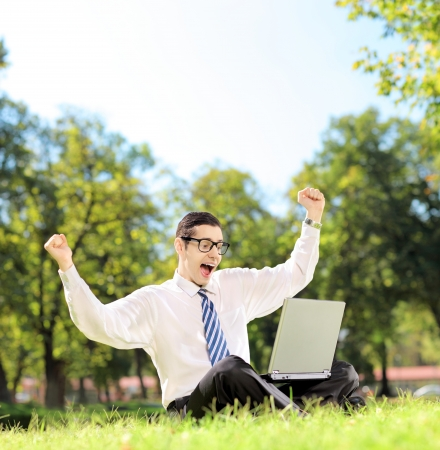 Young man cheering and watching TV on a laptop in a park on a sunny day, shot with a tilt and shift lens photo