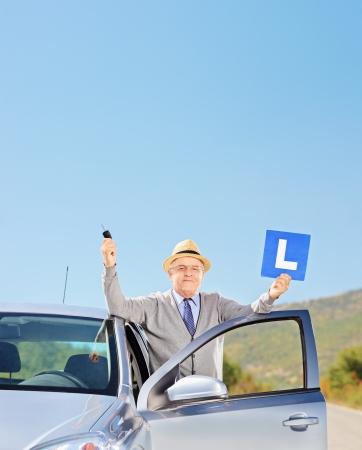 Lachende volwassen man die naast zijn auto met een L teken en autosleutel na zijn rijbewijs, buiten, geschoten met een tilt en shift lens Stockfoto