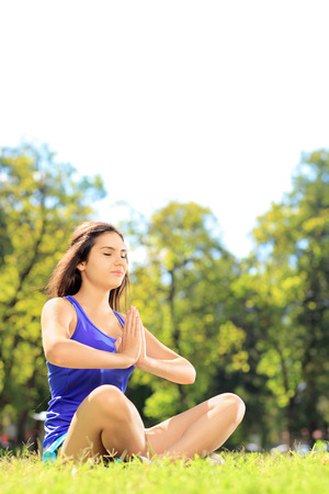 Young female athlete in sportswear doing yoga exercise seated on a green grass in a park Stock Photo - 22658440
