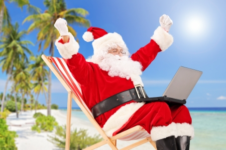 Happy Santa Claus sitting on a chair with laptop and gesturing happiness, on a tropical beach Stock Photo