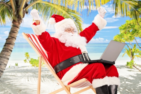 Happy Santa Claus on a chair working on a laptop and gesturing happiness, on a tropical beach photo